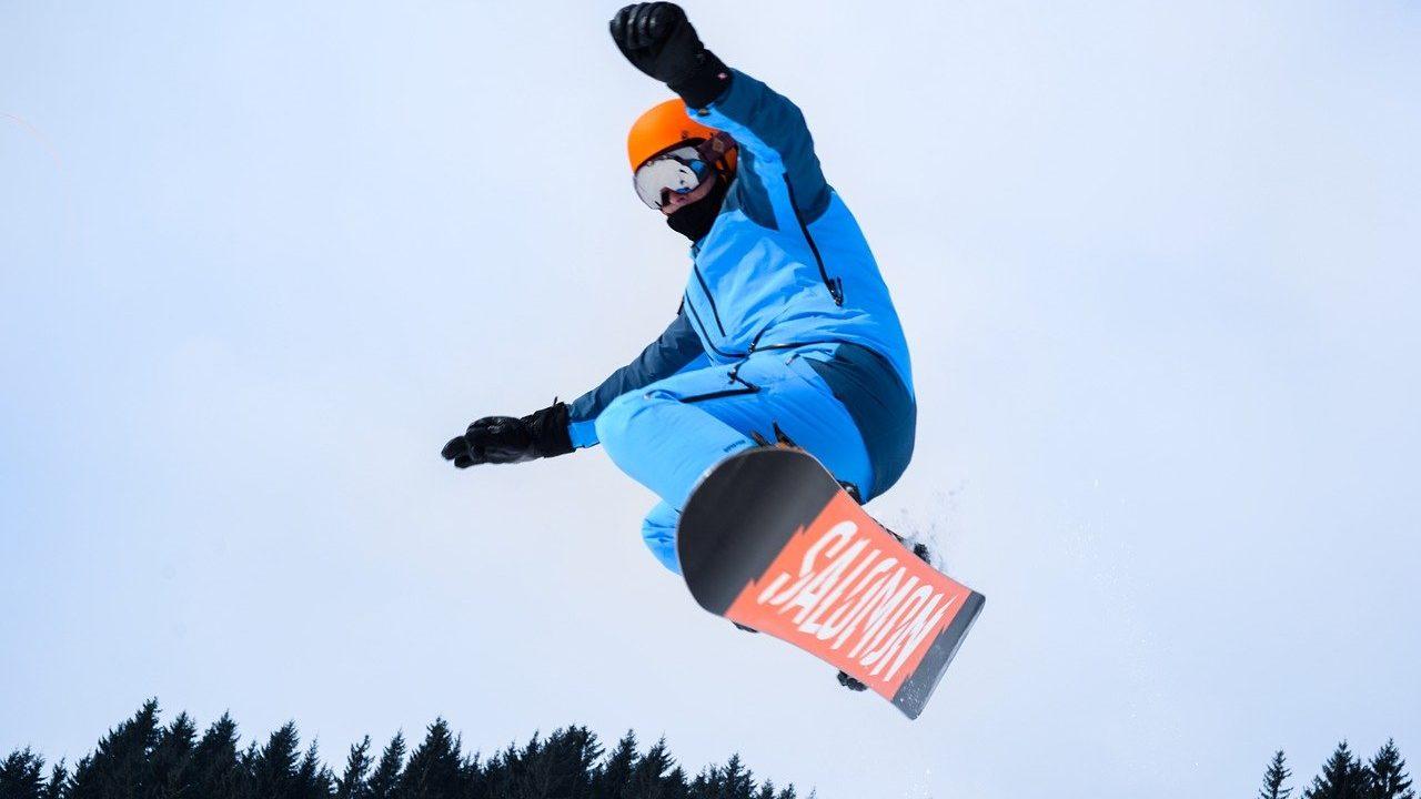 スノーボードでジャンプしている男性の画像